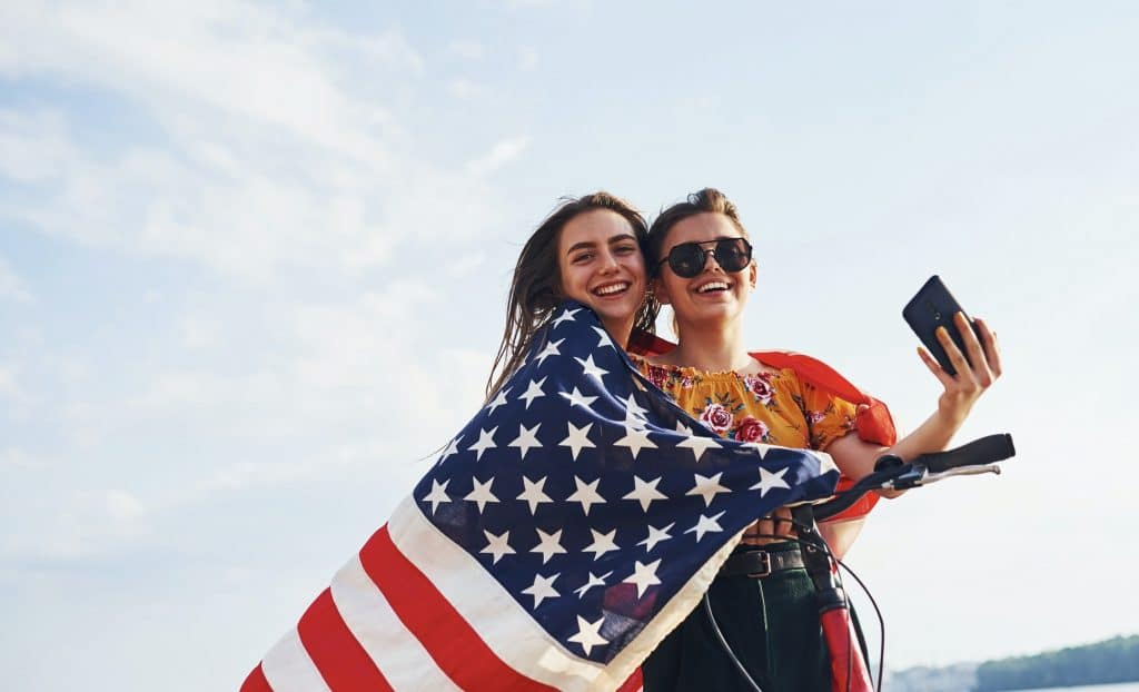 Two patriotic cheerful women with bike and USA flag in hands makes selfie